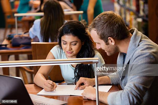 College student tutoring teenage girl in crowded public library