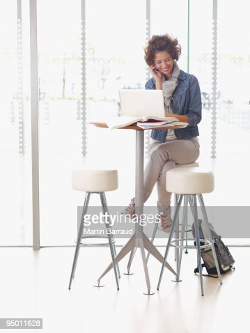 College student using laptop and cell phone at table : Stock Photo