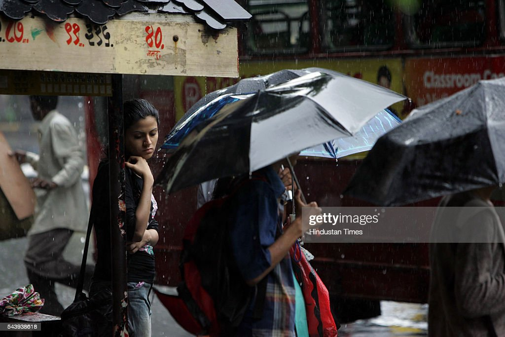 A college student waits for her bus to arrive near Shivaji Park on July 21, 2005 in Mumbai, India. Heavy rains lashed across the city leaving most of the areas around the city in a flooded state.