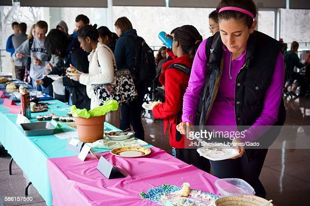 College students crowd around the long table to try various types of cake at the Edible Book Festival April 2014 Courtesy Eric Chen