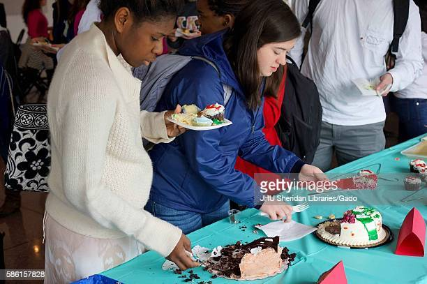 College students cut and eat cake at the 2014 Edible Book Festival a literary cake competition on the Homewood campus of the Johns Hopkins University...