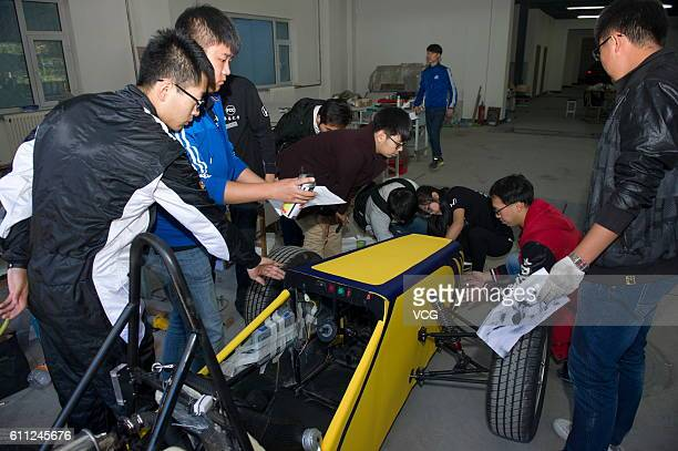 College students debug a yellow racing car at Changchun University on September 28 2016 in Changchun Jilin Province of China Three college teachers...