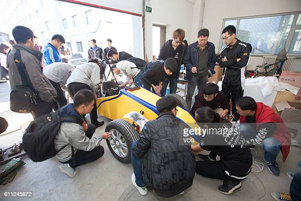 College students fix a yellow racing car at Changchun University on September 28 2016 in Changchun Jilin Province of China Three college teachers and...