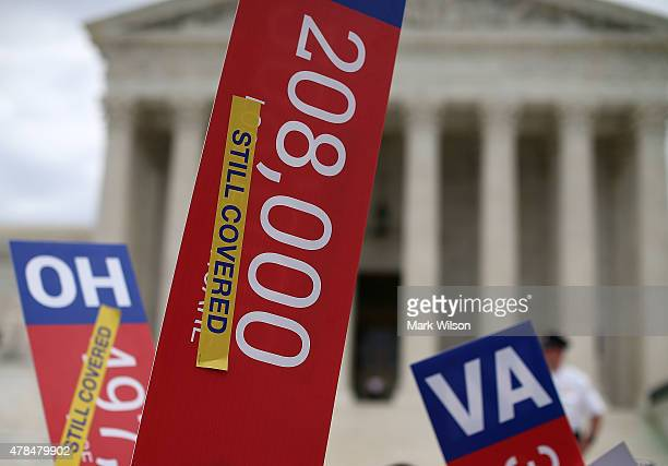 College students hold up signs in front of the US Supreme Court after a ruling was announced in favor of the Affordable Care Act June 25 2015 in...