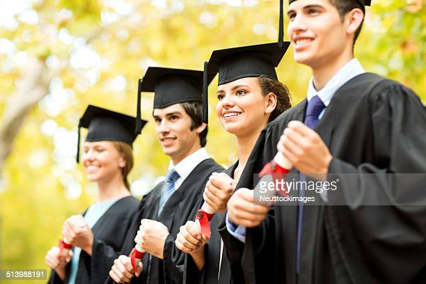 College Students Holding Certificates On Graduation Day