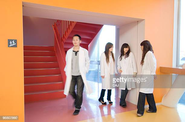 College Students in White Coat Talking at Staircase Landing
