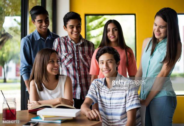 College students looking at one student and smiling