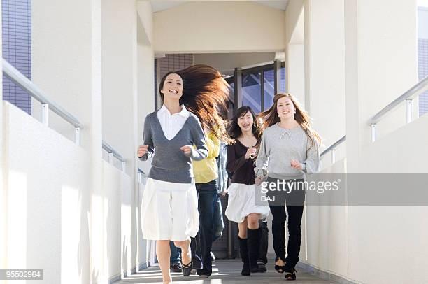 College Students Running in Corridor