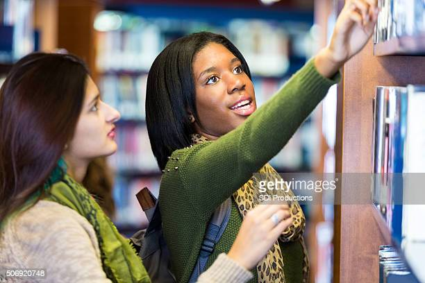 College students searching for book together in library