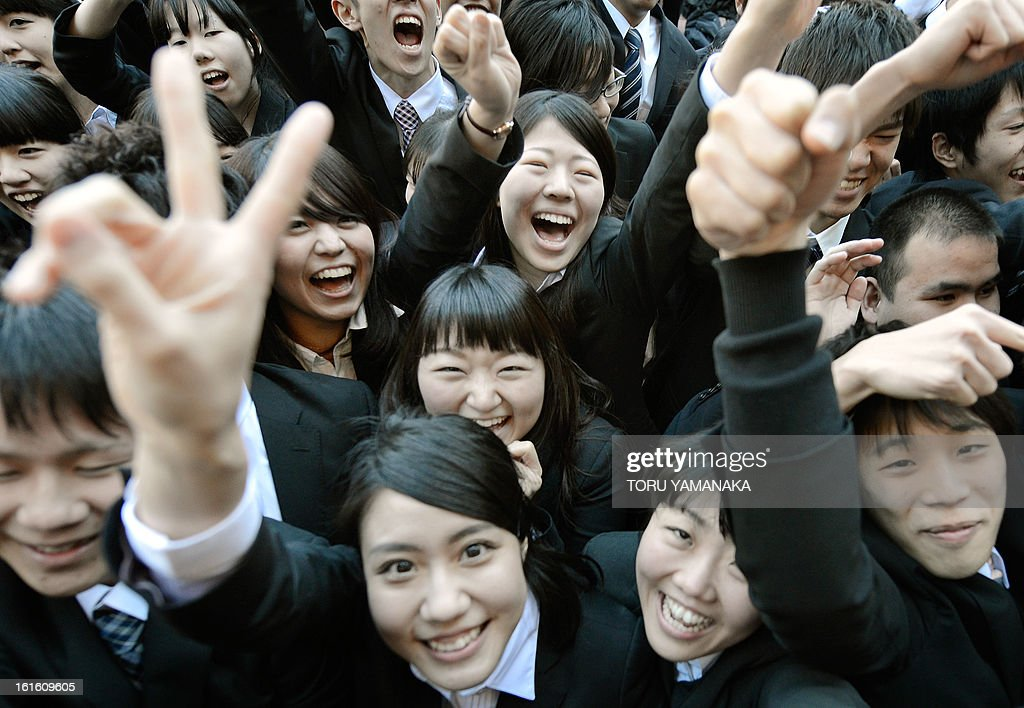 College students shout as they raise their arms at the start of a job hunting ceremony in Tokyo on February 13, 2013. Some 1,500 students, who will graduate from schools in March 2014, attended the annual ceremony which aims to encourage future graduates to look for jobs. AFP PHOTO/Toru YAMANAKA