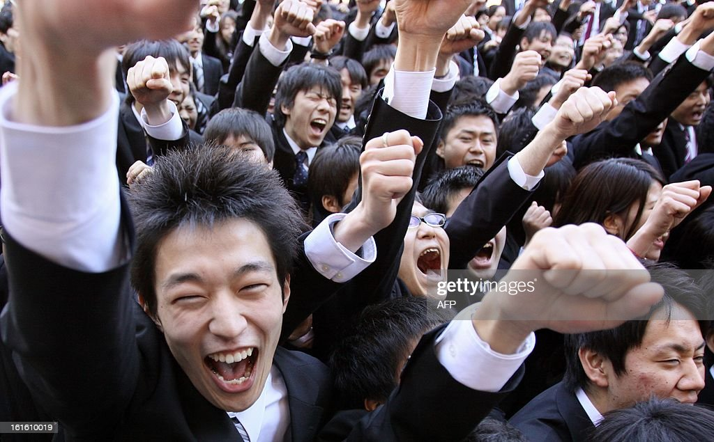 College students shout as they raise their arms at the start of a job hunting ceremony in Tokyo on February 13, 2013. Some 1,500 students, who will graduate from schools in March 2014, attended the annual ceremony which aims to encourage future graduates to look for jobs. AFP PHOTO/Rie ISHII