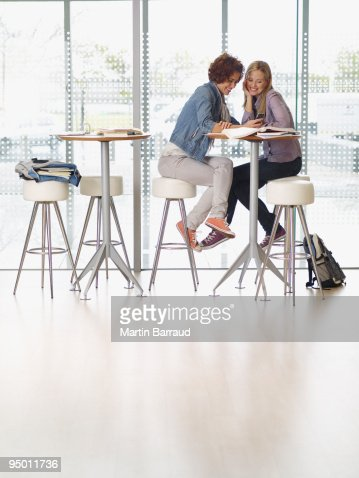 College students sitting at table using cell phone : Stock Photo
