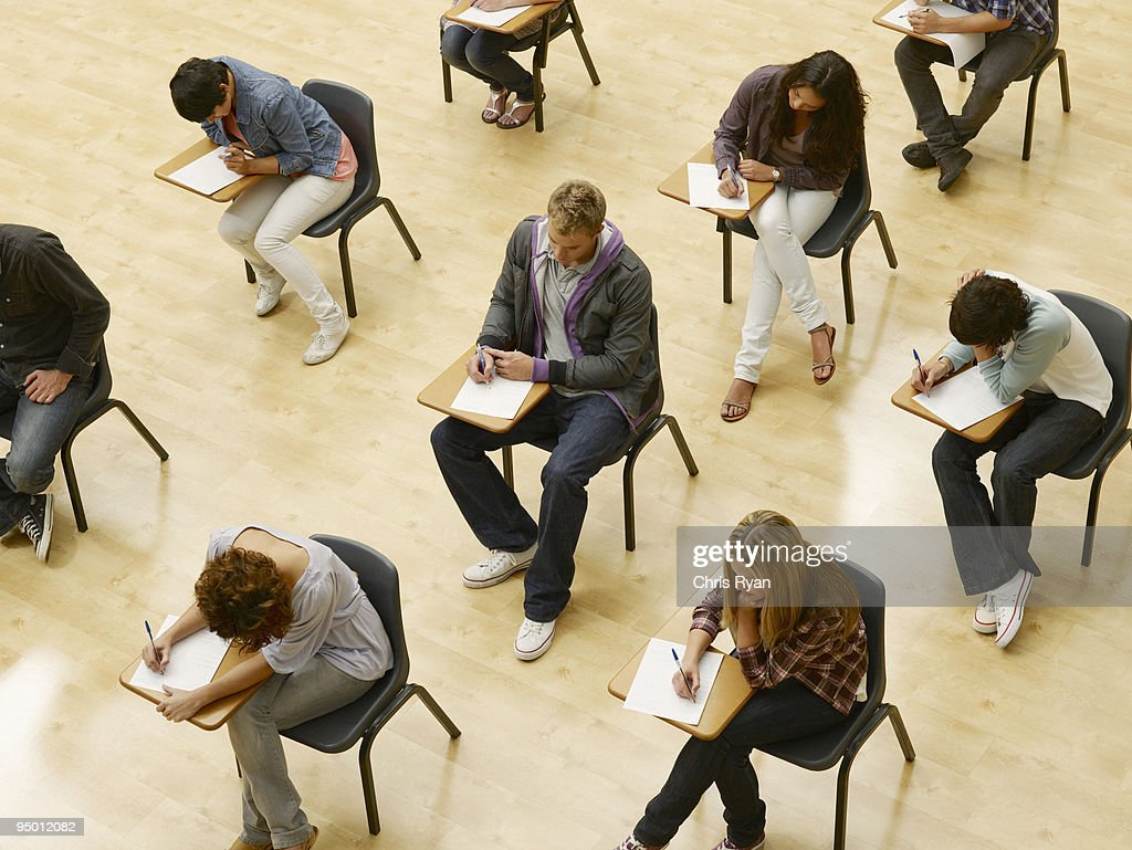 College students taking test in classroom : Foto de stock