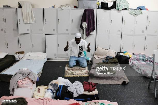 Collen Harris a practicing Muslim and a displaced resident from the island of Barbuda prays inside a shelter at a cricket stadium on December 7 2017...