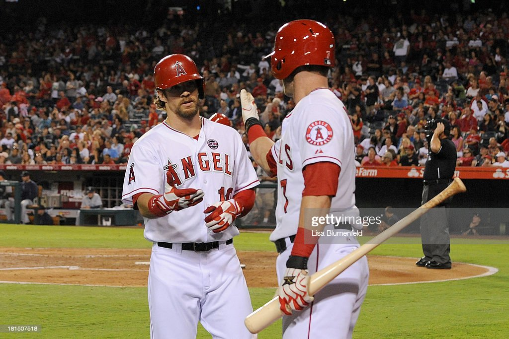 <a gi-track='captionPersonalityLinkClicked' href=/galleries/search?phrase=Collin+Cowgill&family=editorial&specificpeople=6888953 ng-click='$event.stopPropagation()'>Collin Cowgill</a> #19 of the Los Angeles Angels of Anaheim is congratulated by teammate <a gi-track='captionPersonalityLinkClicked' href=/galleries/search?phrase=Andrew+Romine&family=editorial&specificpeople=2338123 ng-click='$event.stopPropagation()'>Andrew Romine</a> #7 after hitting a homerun in the fourth inning against the Seattle Mariners at Angel Stadium of Anaheim on September 21, 2013 in Anaheim, California.