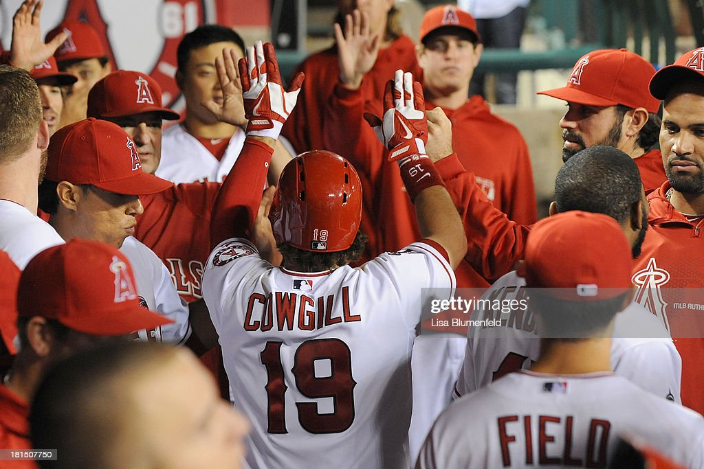 <a gi-track='captionPersonalityLinkClicked' href=/galleries/search?phrase=Collin+Cowgill&family=editorial&specificpeople=6888953 ng-click='$event.stopPropagation()'>Collin Cowgill</a> #19 of the Los Angeles Angels of Anaheim is congratulated by his teammates after scoring in the seventh inning against the Seattle Mariners at Angel Stadium of Anaheim on September 21, 2013 in Anaheim, California.