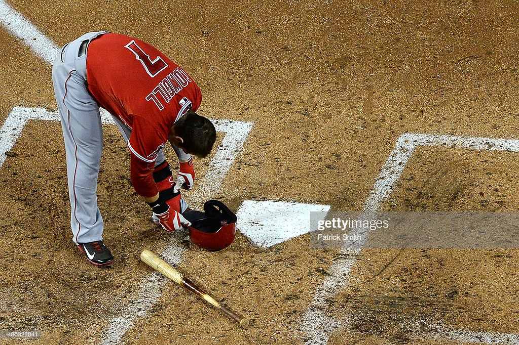 Collin Cowgill of the Los Angeles Angels of Anaheim takes off his shin guard after striking out against the Washington Nationals in the fifth inning...