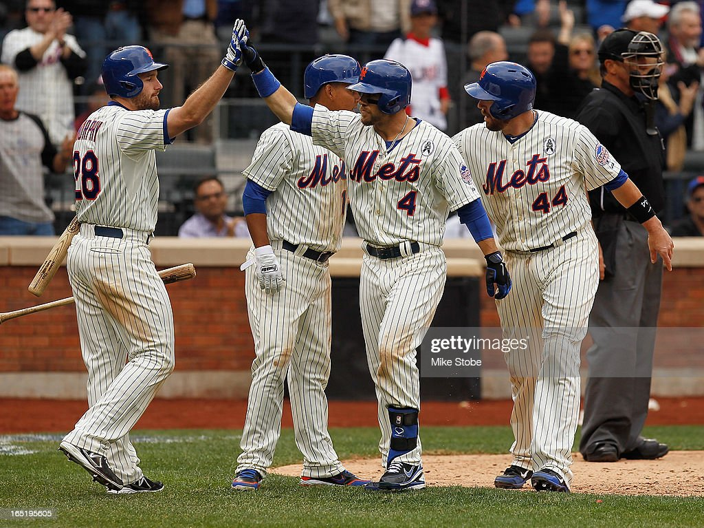 Collin Cowgill #4 of the New York Mets is greeted by John Buck #44, Daniel Murphy #28 and Ruben Tejada #11 after hitting a grand slam in the seventh inning against the San Diego Padres on opening day at Citi Field on April 1, 2013 in the Flushing neighborhood of the Queens borough of New York City.