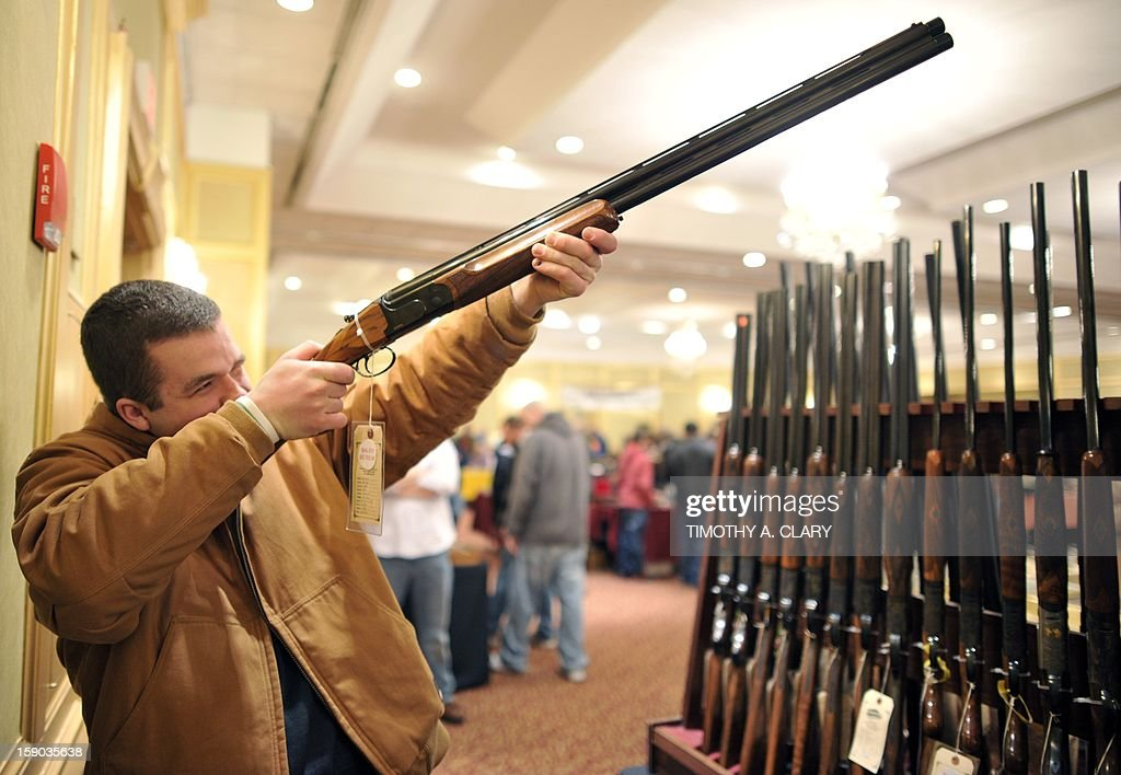 Collin McCarthy of Monroe, Connecticut, looks at a shotgun during the 8th Annual East Coast Fine Arms Show in Stamford, Connecticut January 6, 2013. This is the first gun show in Connecticut sine the December 14 shooting that killed 20 children and six teachers from Sandy Hook Elementary School approximatley 40 miles away in Newtown, Ct. The gun show featured collectible and antique weapons.
