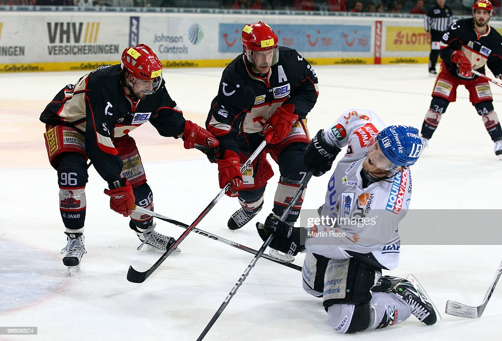 Collin Murphy of Augsburg is blocked by Andre Reiss and Sascha Goc of Hannover during the DEL play off final match between Hannover Scorpions and...