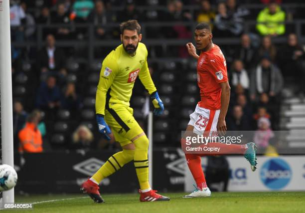 Collin Quaner of Huddersfield Town scores the opening goal past Scott Carson of Derby County during the Sky Bet Championship match between Derby...