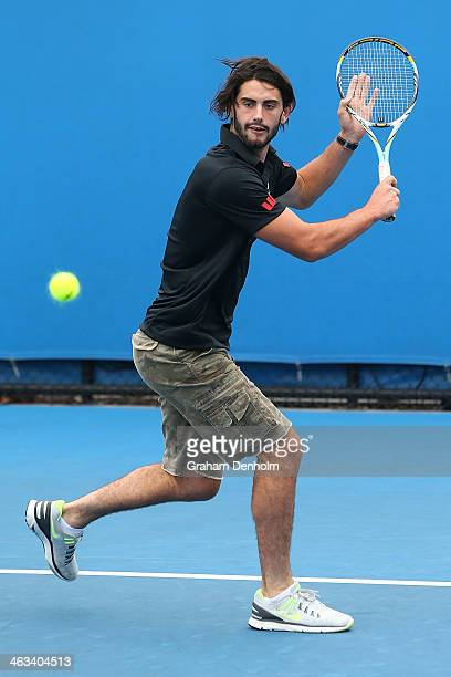Collingwood AFL player Brodie Grundy tries his hand at tennis under the guidance of Kevin Anderson of South Africa during day 6 of the 2014...