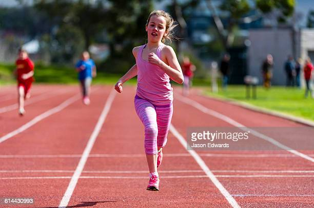 A girl runs along the track during a race at an elementary school athletics competition.