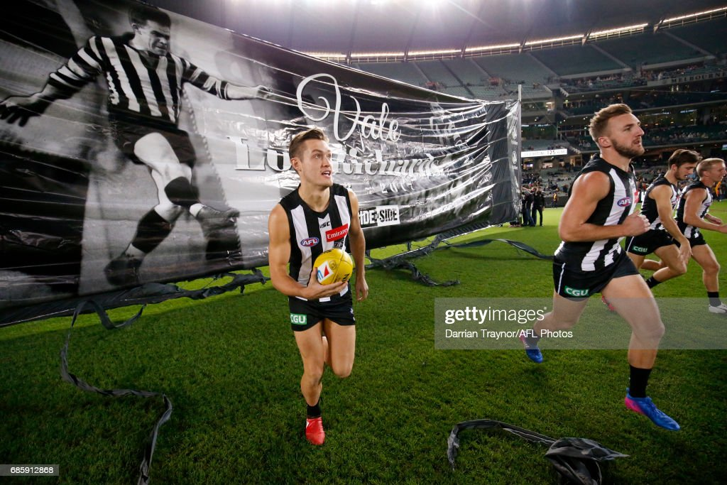 Collingwood players run through the banner before the round nine AFL match between the Collingwood Magpies and the Hawthorn Hawks at Melbourne Cricket Ground on May 20, 2017 in Melbourne, Australia.