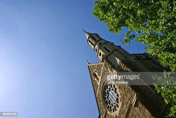 A church steeple rises above the trees on a clear summers day.