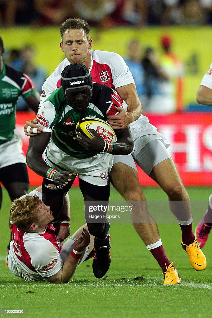 Collins Injera of Kenya is tackled by John Brake and Christian Lewis-Pratt of England in the final cup match between England and Kenya during the 2013 Wellington Sevens at Westpac Stadium on February 2, 2013 in Wellington, New Zealand.