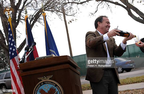 AURORA ColoColorado congressman Ed Perlmutter lifts a bottle of sparkling cider not champagne to toast the beginning of construction He and...