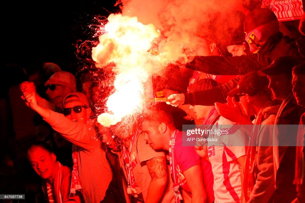 Cologne fans light flares inside the stadium during the UEFA Europa League Group H football match between Arsenal and FC Cologne at The Emirates Stadium in London on September 14, 2017. / AFP PHOTO / Adrian DENNIS
