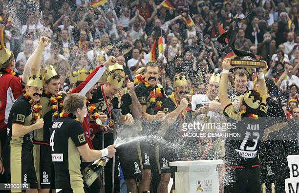 Germany's teammates all wearing crowns and moustaches celebrate with the trophy on the podium after their final match Germany vs Poland of the Men's...