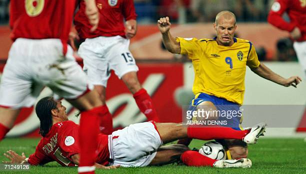 Swedish midfielder Freddie Ljungberg is tackled by English defender Rio Ferdinand during the opening round Group B World Cup football match Sweden vs...