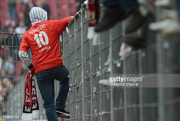 A Cologne supporter stands in front of a fence after the German first division Bundesliga football match between 1 FC Cologne and FC Bayern Muenchen...