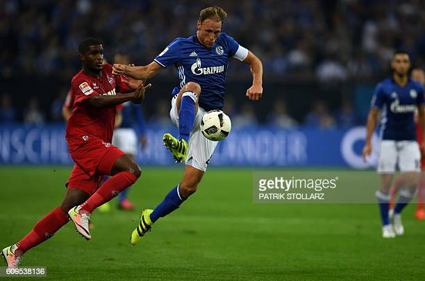Cologne's French striker Anthony Modeste and Schalke's defender Benedikt Hoewedes vie for the ball during the German first division Bundesliga...