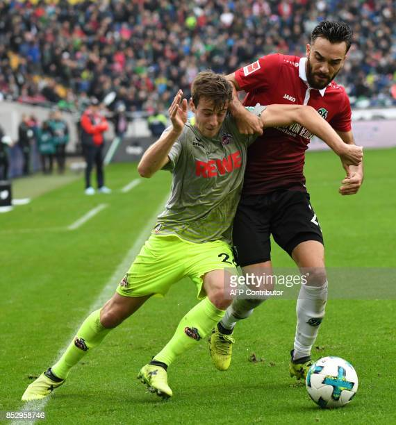 Cologne's German defender Lukas Kluenter and Hanover's Turkish forward Kenan Karaman vie for the ball during the German first division Bundesliga...