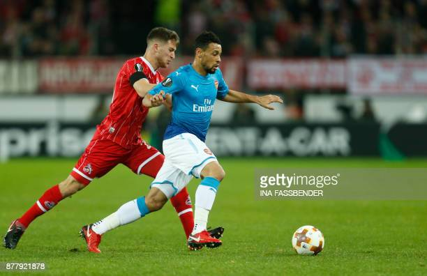 Cologne's German midfielder Salih Ozcan and challenges with Arsenal's French midfielder Francis Coquelin vie for the ball during the UEFA Europa...