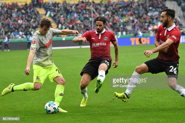 Cologne's German midfielder Salih OzcanHanover's Austrian forward Martin Harnik and Hanover's Turkish forward Kenan Karaman vie for the ball during...