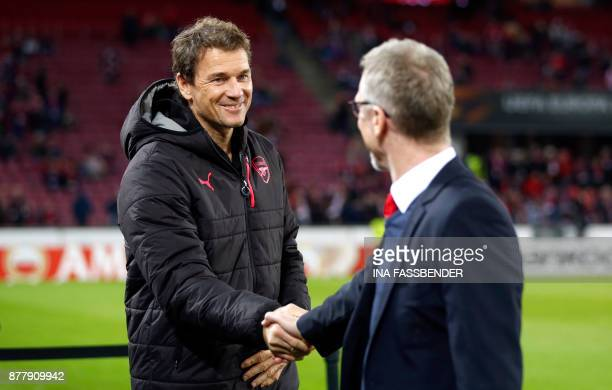 Cologne's head coach Peter Stoeger shakes hands with Arsenal's assistant coach Jens Lehmann the UEFA Europa League football match 1 FC Cologne v...