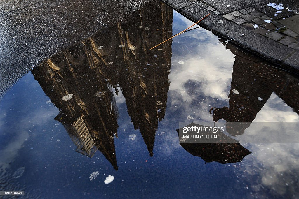Cologne's landmark the Cathedral reflects in a puddle in Cologne, western Germany on December 25, 2012.