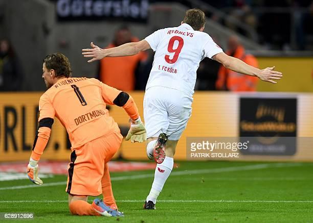 Cologne's Latvian striker Artjoms Rudnevs celebrates scoring the first goal as Dortmund's goalkeeper Roman Weidenfeller gets up during the German...