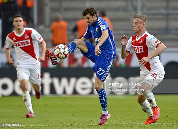 Cologne's midfielder Yannick Gerhardt vies for the ball with Schalke's Swiss midfielder Tranquillo Barnetta during the German first division...