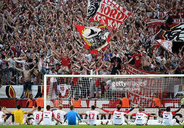 Cologne's players celebrate with their fans after the German First division Bundesliga football match 1 FC Koeln vs Borussia Dortmund on October 18...