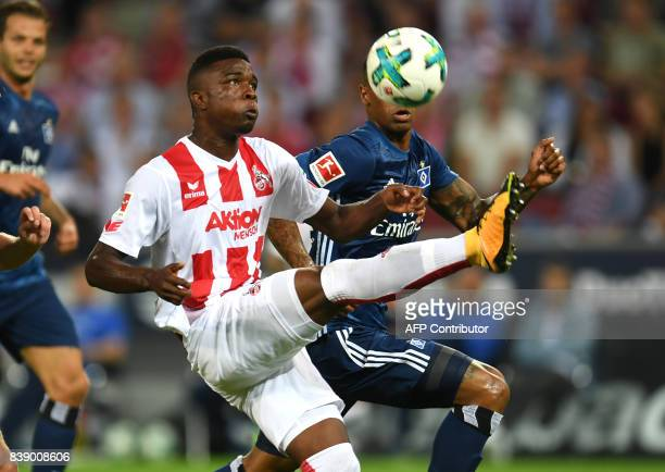 Cologne's striker Jhon Cordoba and Hamburg's Brazilian midfielder Walace vie for the ball during the German first division Bundesliga football match...