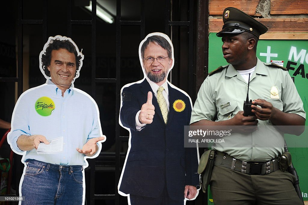 A Colomabian policeman stands next to the images of Colombian presidential candidate for the Green Party Antanas Mockus (C) and his running mate Sergio Fajardo in Medellin, Antioquia department, Colombia on May 27, 2010. Colombia will hold presidential elections next May 30, and according to polls, a run-off election between Mockus and Juan Manuel Santos for the ruling National Unity Party, will take place on June 20. AFP PHOTO/ Raul ARBOLEDA