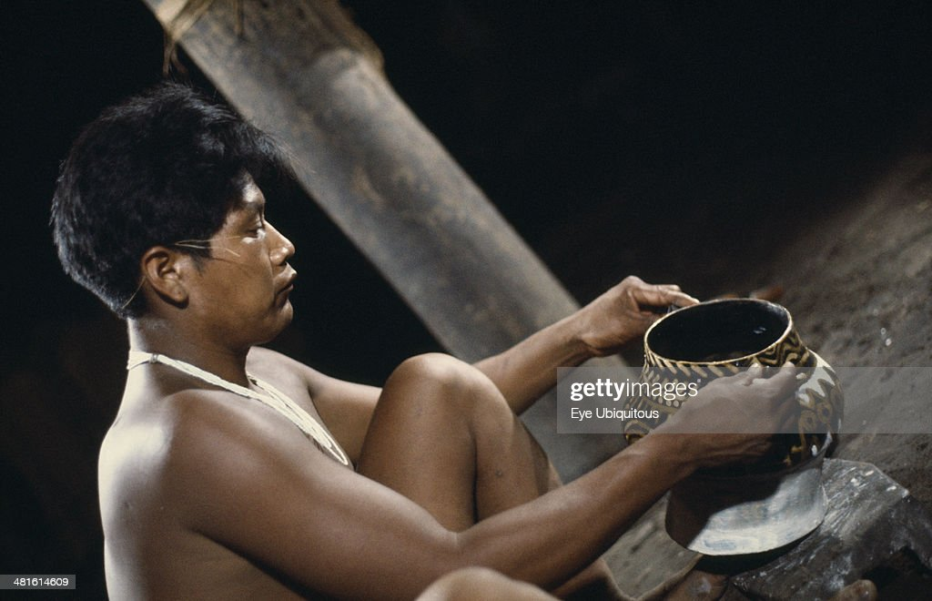 Colombia North West Amazon Tukano Indigenous People Barasana tribesman Pacico a shaman painting clay design onto yaje pot used to hold hallucinogenic...