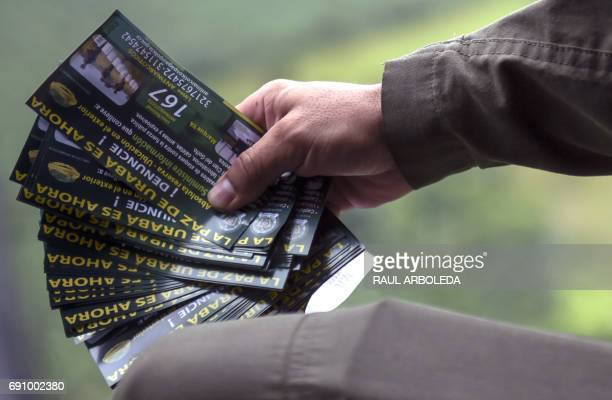 A Colombian antinarcotics police officer holds pamphlets to be thrown from a helicopter offering rewards for information leading to the capture of...