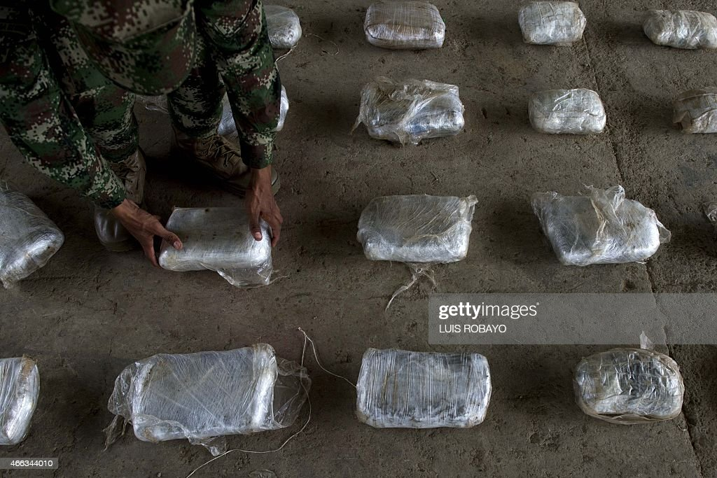A Colombian Army soldier arranges packages of seized cocaine during a press conference at a Military Base in Bahia Solano department of Choco...