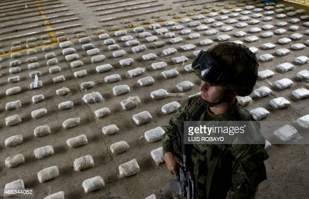 A Colombian Army soldier stands next to packages of seized cocaine during a press conference at a Military Base in Bahia Solano department of Choco...
